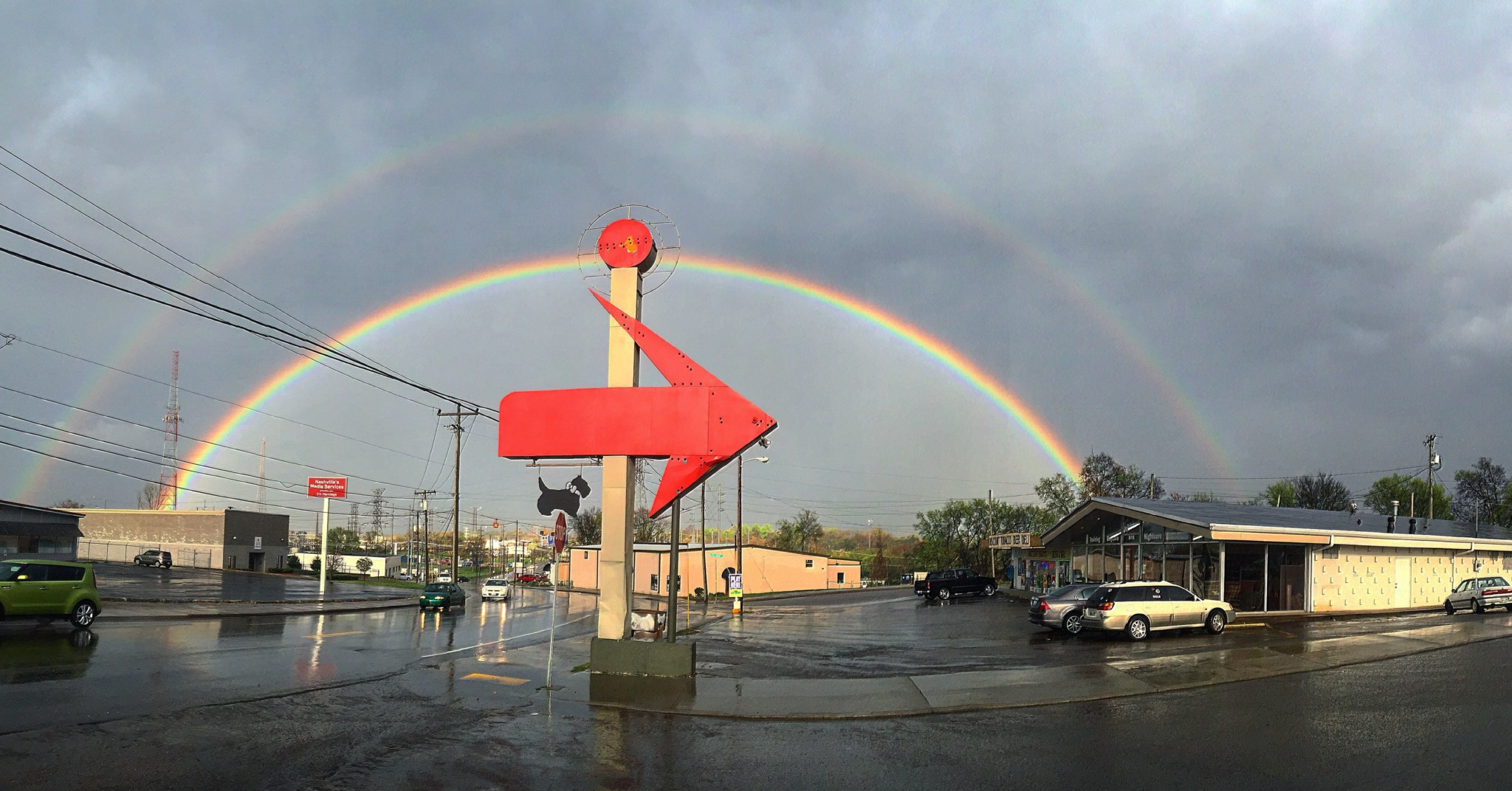 Double Rainbow over large red vintage arrow sign pointing to Red Rover Pet Services Dog Daycare and Boarding